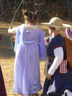 Teaching a young girl to shoot at Buckston Birthday Bash,
